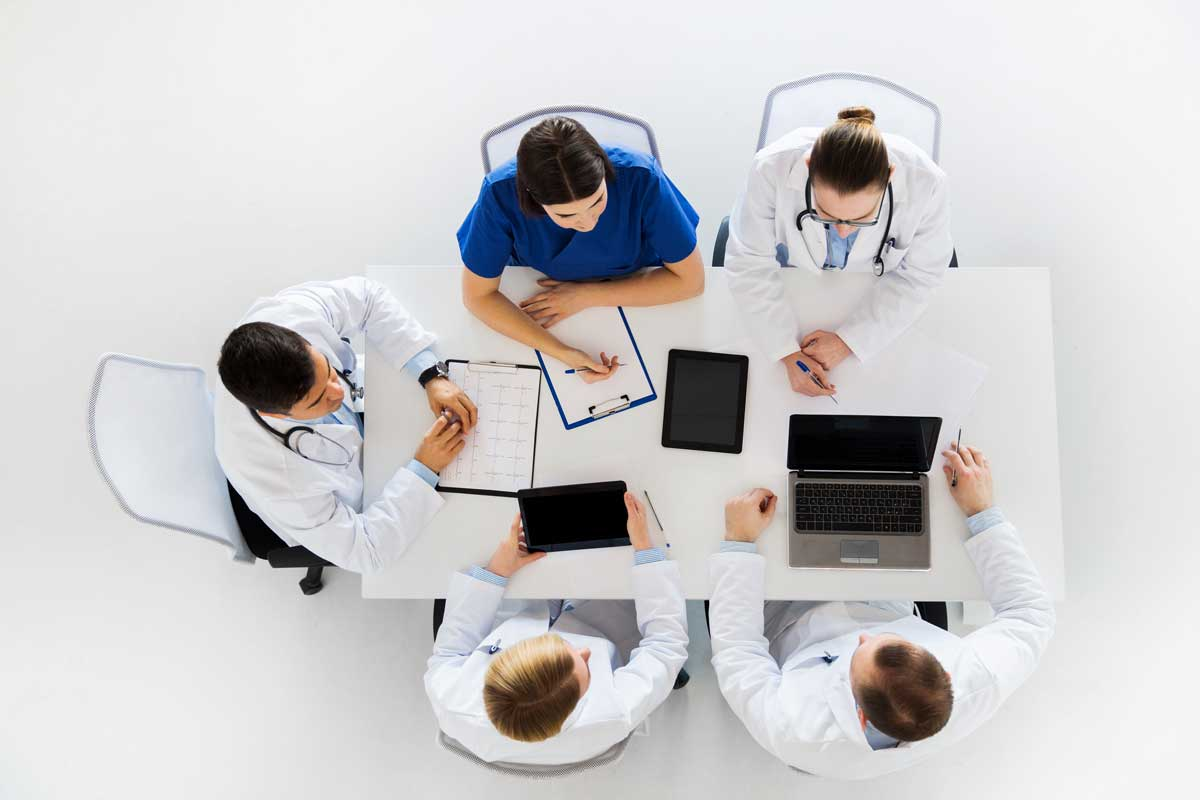Doctors With Cardiogram And Computers At Hospital